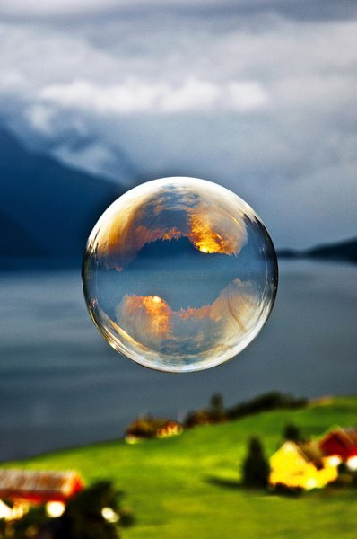 Morning light reflected in a soap bubble over the fjord by Odin Standal