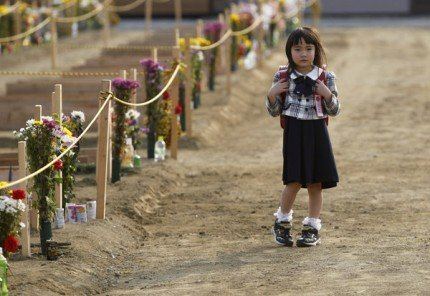 Wakana Kumagai, 6, waits for her mother Yoshiko after visiting the grave of her father, who was killed by the March 11 tsunami